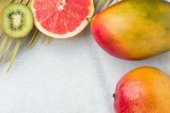 热带自然背景成熟水多的红色芒果切片葡萄柚猕猴桃尖刻的绿色淡黄色棕榈叶 健康食物生活方式 免版税库存照片