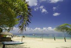 热带离开的白色沙滩有多云蓝天背景 水晶大海和小屋在海滩 库存照片