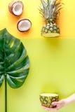 热带水果在手中在黄色背景顶视图大模型的夏天设计的 库存图片