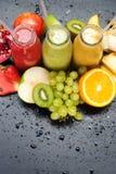 热带水果汁圆滑的人红色绿色黄色 免版税库存照片