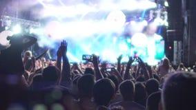 热心人群欣喜和摄制在手机实况音乐音乐会 股票录像