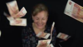 热心妇女投掷钞票在黑背景,愉快的大金钱的五千卢布慢动作股票 股票录像
