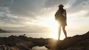 热心有旅行背包徒步旅行者女性敬佩的惊人的日落正面情感 股票录像