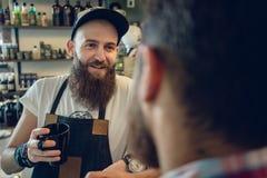 热忱的与他的顾客和朋友的发式专家饮用的咖啡 图库摄影