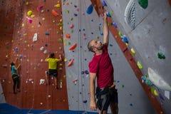 热忱的运动员和教练员上升的墙壁在俱乐部 库存图片