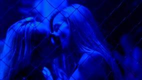 热情地亲吻在金属链子篱芭,一夜情后的两名肉欲的妇女 免版税图库摄影