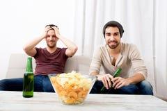 热情地看电视用啤酒和芯片的两个朋友 库存照片