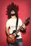 热情的吉他弹奏者尖叫与美丽的长的卷发pl 免版税库存照片