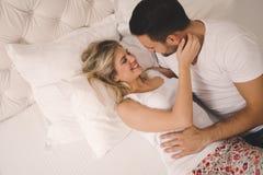 热情的夫妇爱抚在床上 免版税库存照片
