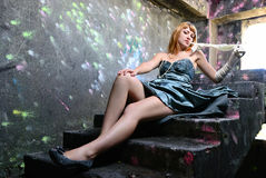 晚礼服的女孩在一架老梯子说谎 免版税库存图片