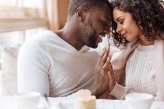 热情的非裔美国人的在咖啡馆的夫妇感人的手 免版税库存照片