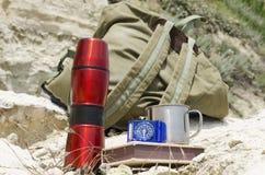 热水瓶、笔记本、指南针和metall杯子在岩石,背包特写镜头作为背景 免版税库存照片