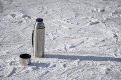 热水瓶在与一个杯子的冰站立热的茶 免版税库存照片