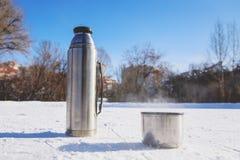 热水瓶在与一个杯子的冰站立热的茶 免版税库存图片