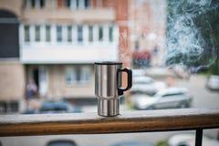 热水瓶杯子在阳台栏杆 库存图片