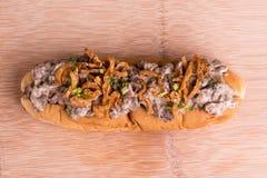 热狗冠上了用焦糖的葱、牛肉和切达乳酪调味汁 库存照片