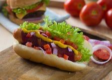 热狗和烟肉服务用芥末蕃茄和大量bac 图库摄影