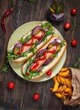 热狗在船上用调味汁和炸薯条在一张木桌上 库存照片