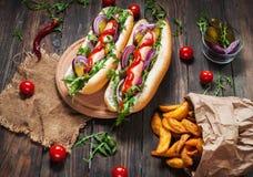 热狗在船上用调味汁和炸薯条在一张木桌上 库存图片