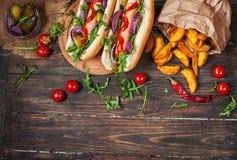 热狗在船上用调味汁和炸薯条在一张木桌上 免版税库存照片