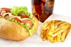 热狗用在餐巾的炸薯条与杯可乐 免版税图库摄影