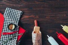 热狗用芥末、番茄酱和蛋黄酱在木背景 顶视图 免版税库存图片