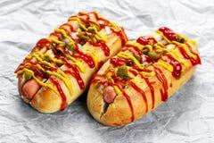 热狗用香肠、葱、腌汁芥末和番茄酱 免版税图库摄影