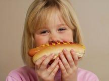 热狗的女孩微笑的一点 免版税库存图片