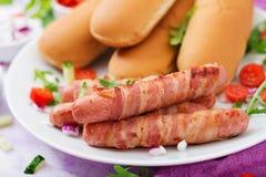 热狗的成份用香肠 烟肉、黄瓜、蕃茄和红洋葱 库存照片