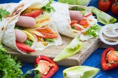 热狗-三明治用在皮塔饼、韩国红萝卜、蕃茄、葱、荷兰芹和胡椒的香肠 木背景 免版税图库摄影