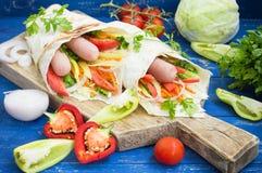 热狗-三明治用在皮塔饼、韩国红萝卜、蕃茄、葱、荷兰芹和胡椒的香肠 木背景 库存照片