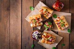 热狗-与墨西哥辣调味汁的三明治在木背景 图库摄影