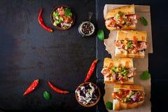 热狗-与墨西哥辣调味汁的三明治在黑暗的背景 库存照片