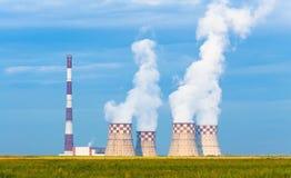 热电厂有冷却塔的Ñ€igh管子在一个绿色草甸 图库摄影