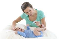 热病,对婴孩的Mumn测量的温度 免版税库存图片