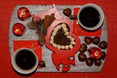 热的咖啡、两个杯子在桌上和咖啡豆-愉快的情人节 免版税库存照片