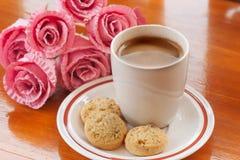 热的咖啡、曲奇饼和桃红色花 免版税库存照片