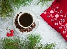 热的咖啡、红色温暖的套头衫和礼物与一把红色弓在多雪的背景 免版税库存照片