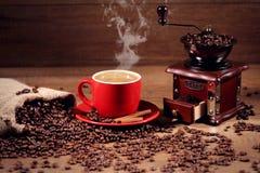 热的咖啡和咖啡豆在磨咖啡器背景  免版税库存图片