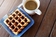 热的咖啡和奶蛋烘饼用巧克力汁在木桌背景 免版税库存图片