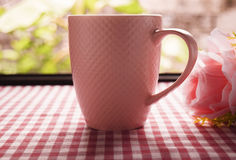 热的咖啡和甜桃红色玫瑰在桌上 免版税库存照片