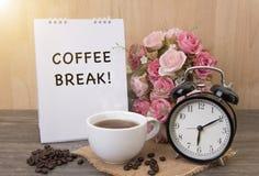 热的咖啡和闹钟在木桌上与玫瑰色花 免版税库存图片