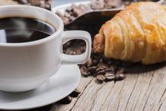 热的咖啡和面包在木背景 免版税图库摄影