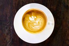 热的咖啡拿铁顶视图在黑暗的木背景的 库存图片
