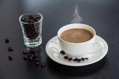 热的咖啡杯和豆在玻璃 免版税库存图片