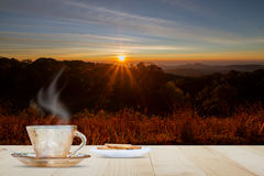 热的咖啡杯和饼干在木台式在被弄脏的草甸和山与日出和火光背景 免版税库存照片