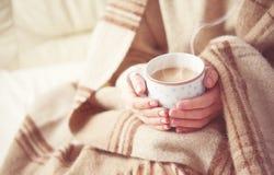 热的咖啡温暖在女孩的手上的杯 免版税库存照片