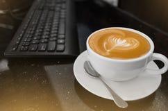 热的咖啡热奶咖啡拿铁艺术顶视图在白色杯子的在会议桌上 库存照片