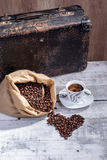 热的咖啡用咖啡豆溢出了在形状的袋子外面 图库摄影