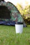 热的咖啡饮料,在绿草的白色一次性杯子 库存照片
